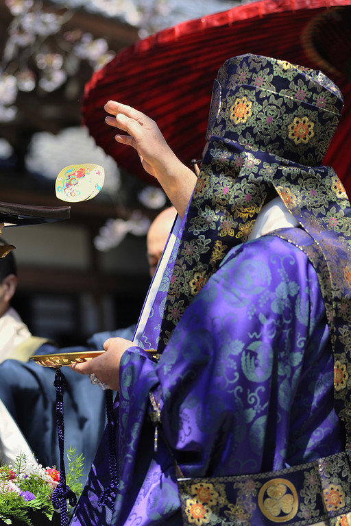 The head officiant casts decorated paper lotus petals.