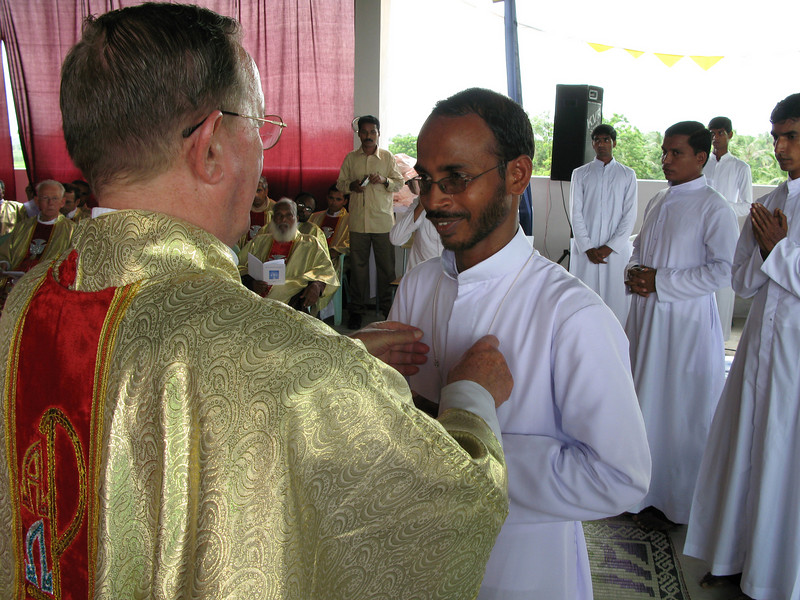 Br. Aji receives his profession cross.