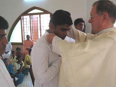 Fr. Martin places the profession cross around Bhaskar's neck.