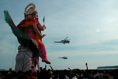 Indian Navy provides ariel support in case of any eventually.  Ganesh Chaturthi [Birthday Of Lord Ganesh] being celebrated by the immersion of Ganesh idols in the Chowpatty beach, Mumbai, India.