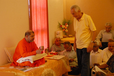 Swami Tejomayanandaji talking with people in his room.