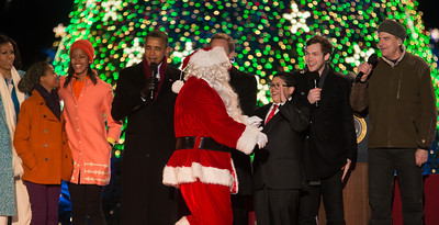 """President Barack Obama and The First Family appear onstage with Santa and entertainers at the conclusion of the 90th annual National Christmas Tree Lighting Ceremony on the Ellipse, just south of the White House in Washington D.C. on December 6, 2012. In photo, Santa greets young actor Rico Rodriguez of ABC's """"Modern Family"""".  (Photo by Jeff Malet)"""