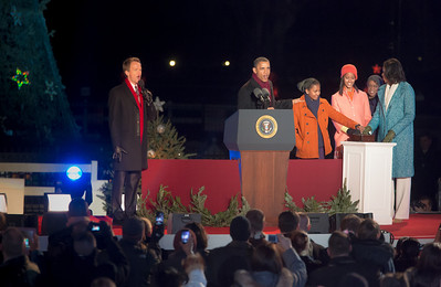 First daughter Sasha Obama (third from left) has her hand on the button to light the National Christmas Tree. President Barack Obama, joined by the First Lady, their two daughters, Sasha and Malia, and the First Grandmother appeared before an estimated crowd of 17,000 on the Ellipse, just south of the White House in Washington D.C. on December 6, 2012 for the 90th annual tree lighting ceremony. TV star Neil Patrick Harris (left) hosted the event. (Photo by Jeff Malet)