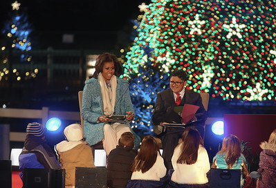 """First lady Michelle Obama, left, joined by Rico Rodriguez of """"Modern Family,"""" reads """"Twas the Night Before Christmas"""" to children gathered on the stage of the National Christmas Tree Lighting Ceremony on the Ellipse just south of the White House  in Washington D.C. on December 6, 2012. It was the 90th annual edition of the tree lighting ceremony. (Photo by Jeff Malet)"""