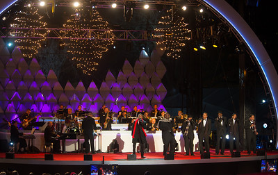 """Singer, songwriter and producer Kenny """"Babyface"""" Edmonds (center in red scarf) entertains at the 90th annual lighting of the National Christmas Tree. President Barack Obama and the First Family flicked the switch to light up the tree before an estimated crowd of 17,000 on the Ellipse, south of the White House in Washington D.C. on December 6, 2012.  (Photo by Jeff Malet)"""