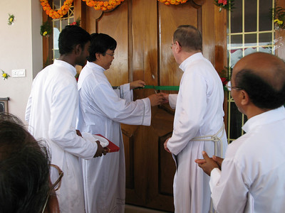 Fr. Madya, General Councilor, cuts the ribbon at the door.