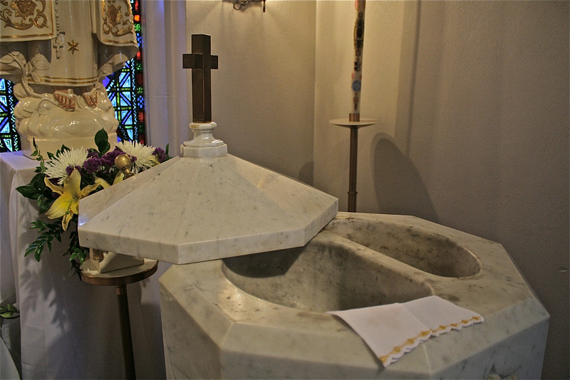 The instructions for performing a baptism describe the use of the hole on the right of the font. Care must be taken to avoid having the baptismal water return to the font. So the extra hole is to receive any water that drips down after it is poured on the person's head.