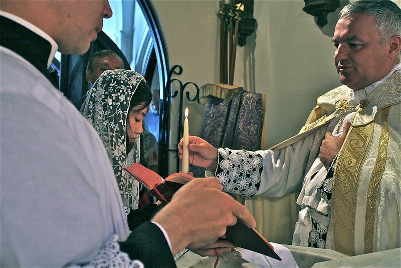 After lighting a candle at the Pascal candle, Canon gives it to Jessica. Note that the vestments in the violet penitential color are set aside after the candidate enters the church, and the priest puts on the white vestments of purity and rejoicing.