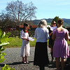 The choir practices chant outdoors before the Mass, on a beautiful sunny day, with rows of grapevines behind them.
