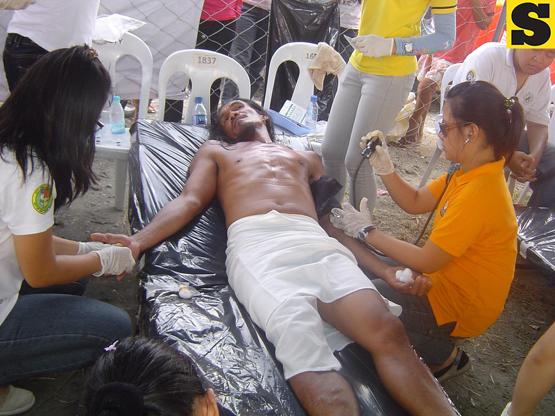 Qucik Aid. Oca Nars volunteers apply first aid treatment to one of the penitents who took part in this year's Holy Week crucifixion.