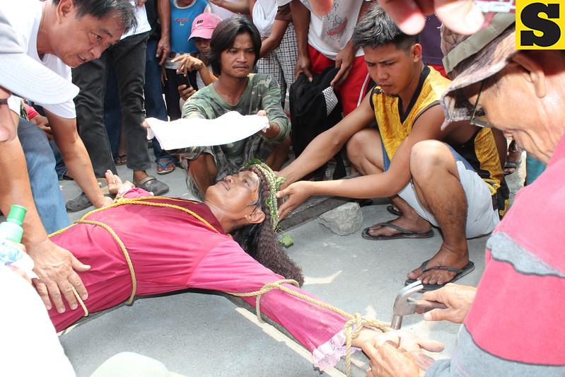 VIA CRUSIS. Monching Calaguas, 42, of Barangay Sta. Barbara is nailed to a wooden cross during rites held in Barangay San Vicente, Bacolor town.