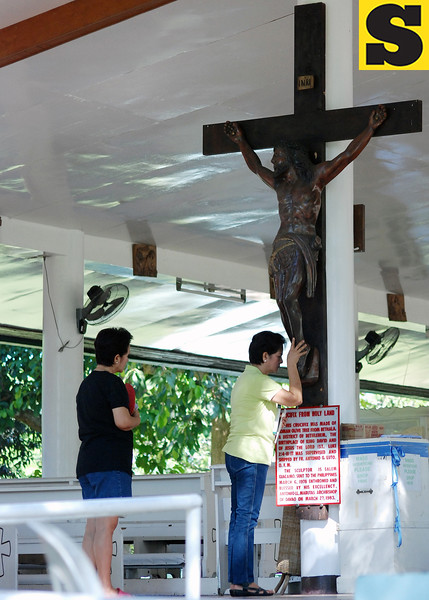 DAVAO. Catholic devotees pray before a big cross at the Shrine of the Holy Infant Jesus of Prague at Shrine Hills in Matina, Davao City on Holy Wednesday. (King Rodriguez)