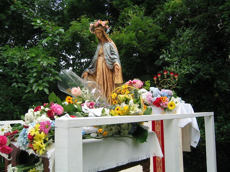 Mary in her honor and Glory, covered with flowers put on by the children of the parish