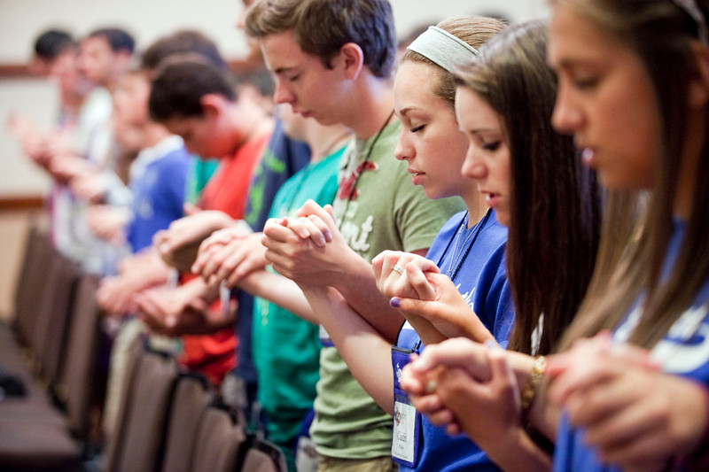 """Caitlin Philips (center) prays the Our Father with her youth group during the Friday evening Mass. 1,400 middle school and high school youth attended the annual Diocesan Catholic Youth Conference on July 13-15, 2012 at the Hyatt DFW Airport. The conference featured Mass, workshops, music, entertainment, prayer and keynote addresses focusing on the theme """"Ignite My Heart, I Burn For You."""""""