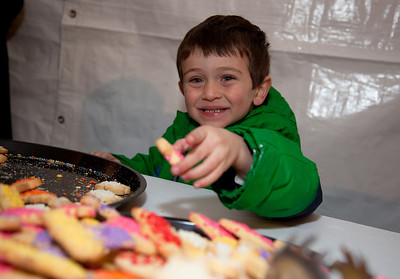 "Brighton Rabin helps himself to some treats at a special lighting ceremony  for the National Hanukkah Menorah, the world's largest, on the Ellipse, just across from the White House on the first night of the eight-day Jewish holiday. Those who attended the lighting were treated to hot Hanukkah latkes and doughnuts. Free personal menorah kits were also distributed. The first candle was lit on Tuesday, December 20, 2011 by special guest, Office of Management and Budget Director Jacob Lew. ""The President's Own"" U.S. Marine Band, and ""The Three Cantors"" performed. The national menorah lighting dates to 1979 when Jimmy Carter was president. Hanukkah celebrates the Jewish Maccabees' military victory over Syrian oppression more than two-thousand years ago. A candle is lit each night of the eight-day celebration, commemorating the miracle of one day's supply of oil lasting a full eight days in the lamp following the rededication of the Holy Temple in Jerusalem. This annual event is sponsored by American Friends of Lubavitch (Chabad). (Photo by Jeff Malet)"