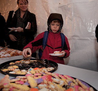 "William Durishin of Columbus OH helps himself to some treats at a special lighting ceremony  for the National Hanukkah Menorah, the world's largest, on the Ellipse, just across from the White House on the first night of the eight-day Jewish holiday. Those who attended the lighting were treated to hot Hanukkah latkes and doughnuts. Free personal menorah kits were also distributed. The first candle was lit on Tuesday, December 20, 2011 by special guest, Office of Management and Budget Director Jacob Lew. ""The President's Own"" U.S. Marine Band, and ""The Three Cantors"" performed. The national menorah lighting dates to 1979 when Jimmy Carter was president. Hanukkah celebrates the Jewish Maccabees' military victory over Syrian oppression more than two-thousand years ago. A candle is lit each night of the eight-day celebration, commemorating the miracle of one day's supply of oil lasting a full eight days in the lamp following the rededication of the Holy Temple in Jerusalem. This annual event is sponsored by American Friends of Lubavitch (Chabad). (Photo by Jeff Malet)"