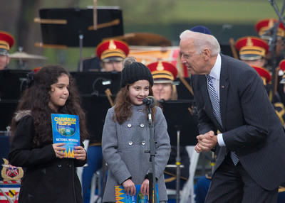 Vice president Joe Biden talks to Simmy Hershkop, 11, of Wooster, Ma., (left) and Basya Fogelman, 9, of Wilkes Barre, Pa, (right) after they read their winning essays on what Hanukkah means to them as they participate in the annual National Menorah Lighting during a ceremony marking the start of the celebration of Hanukkah, on the Ellipse near the White House in Washington, Tuesday, Dec. 16, 2014.