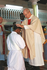 Fr. Tom Fix lays his hands on Fr. Thomas' head.