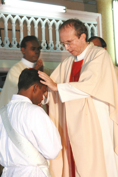 Fr. Beppe lays his hands on Fr. Thomas' head.