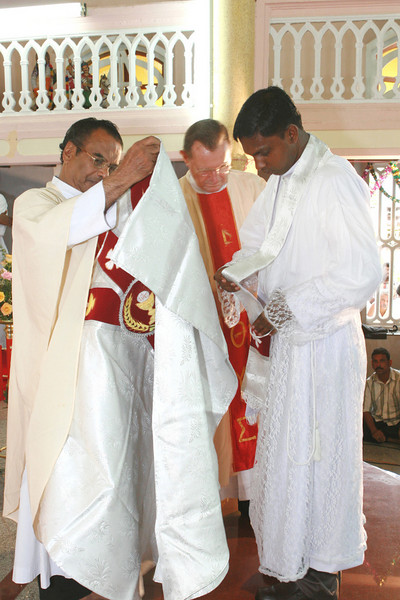 Fr. Thomas is helped being with his vestments.