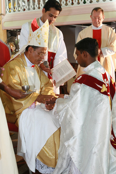 as the bishop anoints his hands with chrism.