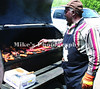 Albert Townsel cooks up the chicken, hot dogs and hambugers at the Resurrection Block Party held at God's Way church on Commerce Rd Saturday. /Mike Adam