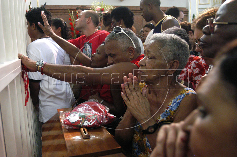 Faithfuls pray in front of an image of Saint George, left, at Saint George Church in Rio de Janeiro, Brazil during celebration of Saint George's Day, April 23, 2006. Thousands of Catholics and worshippers of Afro-Brazilian religions pack churches dedicated to Saint George, widely venerated in Brazil as the African deity Ogum, the warrior god.  (Austral Foto/Renzo Gostoli)