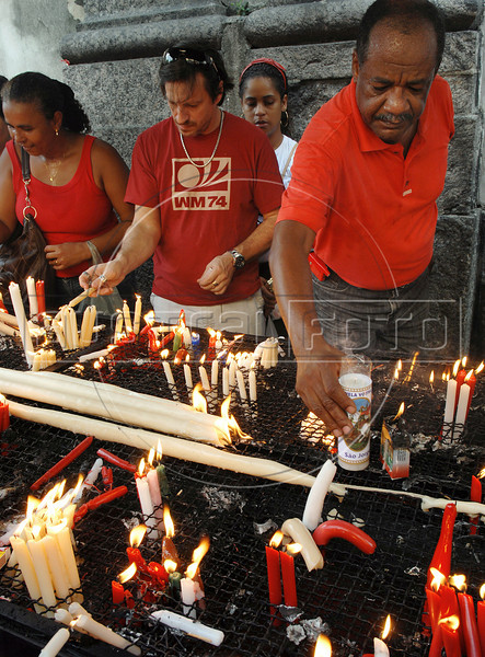 Faithfuls pray and light candles during celebration of Saint George's Day, Rio de Janeiro, Brazil, April 23, 2010. Thousands of Catholics and worshippers of Afro-Brazilian religions pack churches dedicated to Saint George, widely venerated in Brazil as the African deity Ogum, the warrior god. (Austral Foto/Renzo Gostoli)