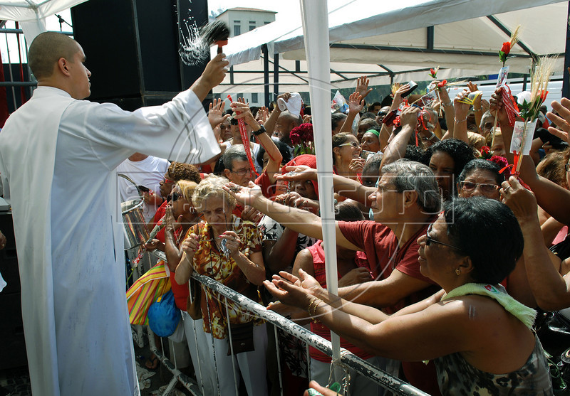 A priest sprinkles holy water to faithfuls during celebration of Saint George's Day, Rio de Janeiro, Brazil, April 23, 2010. Thousands of Catholics and worshippers of Afro-Brazilian religions pack churches dedicated to Saint George, widely venerated in Brazil as the African deity Ogum, the warrior god. (Austral Foto/Renzo Gostoli)