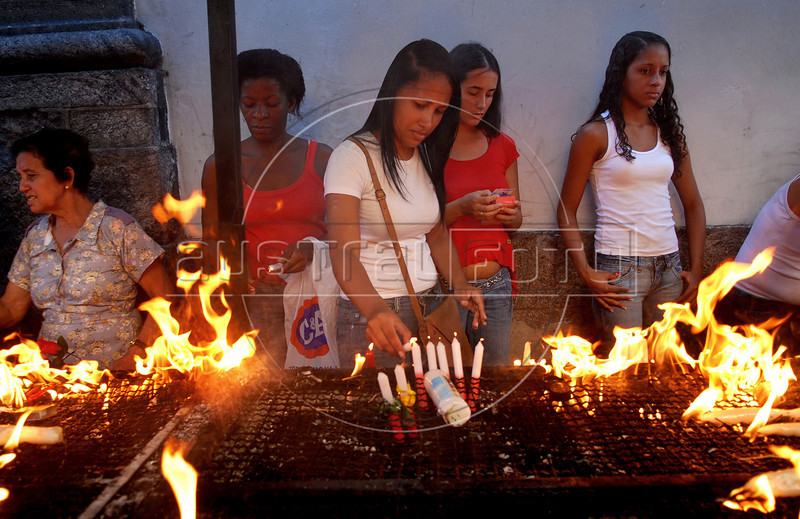 Faithfuls pray and light candles during celebration of Saint George's Day, Rio de Janeiro, Brazil, April 23, 2008. Thousands of Catholics and worshippers of Afro-Brazilian religions pack churches dedicated to Saint George, widely venerated in Brazil as the African deity Ogum, the warrior god.  (Austral Foto/Renzo Gostoli)