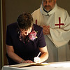 Sister Marla Gipson signing the profession document on the altar. Photo by Pat Morrison