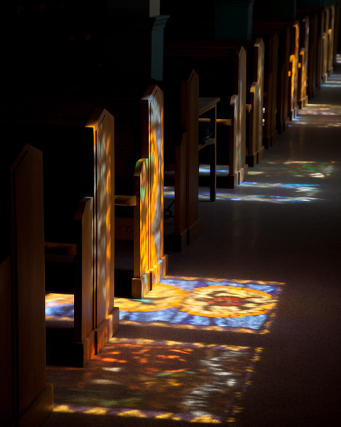 Shadow of stained glass on floor and pews