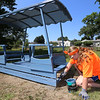 Volunteers from U.M. ARMY (United Methodist Action Reach-out Mission by Youth) help with home repairs at two houses in Chelmsford. Maggie Ray, 18, of Menomonee Falls, Wisconsin, in hier sixth year volunteering with UM Army, helps paint a glider seat in Eileen Bergeron's yard. (SUN/Julia Malakie)