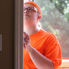 Volunteers from U.M. ARMY (United Methodist Action Reach-out Mission by Youth) help with home repairs at two houses in Chelmsford. Maggie Ray, 18, of Menomonee Falls, Wisconsin, in hier sixth year volunteering with UM Army, inspects the front door frame at Eileen Bergeron's house, where the door was not closing quite right. (SUN/Julia Malakie)