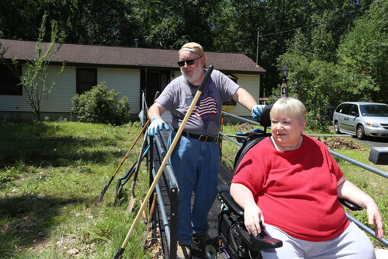 Volunteers from U.M. ARMY (United Methodist Action Reach-out Mission by Youth) help with home repairs at two houses in Chelmsford. Marc and wife Andra Lamarche of Chelmsford, in their front yard, which UM Army was helping clean up. (SUN/Julia Malakie)