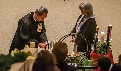 Rev. Makar and Rev. Thickstun light the chalice, the menorah, and the Advent candles.