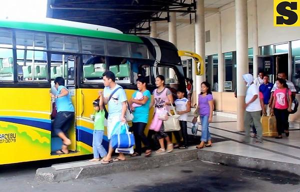A family enters a bus at the Cebu South Bus Terminal.