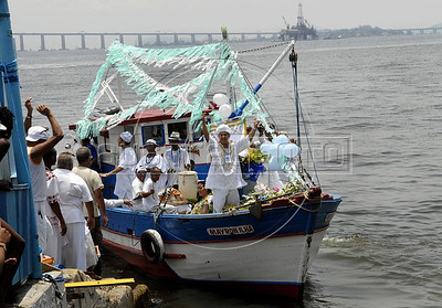 Devotes of Afro-Brazilian religions give offerings by boat into the sea in the Guanabara bay to the African deity of the sea and fertility, Yemanja, Rio de Janeiro, Brazil, February 2, 2011. The festival day corresponds with the Roman Catholic feast of Nuestra Senora de Navegantes, Our Lady of Seafarers, which is also celebrated in Rio de Janeiro. She is also known as the sea-goddess and his devotes give in the sea offerings with flowers, perfumes and wines. Transported by West African slaves to the Americas throughout the hundreds of years of the existence of slavery in the New World. (Austral Foto/Renzo Gostoli)