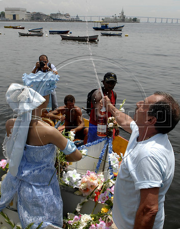 Devotes of Afro-Brazilian religions pour cider over the sculpture of Yemanja, the African deity of the sea and fertility, before give offerings into the sea in the Guanabara bay, Rio de Janeiro, Brazil, February 2, 2011. The festival day corresponds with the Roman Catholic feast of Nuestra Senora de Navegantes, Our Lady of Seafarers, which is also celebrated in Rio de Janeiro. She is also known as the sea-goddess and his devotes give in the sea offerings with flowers, perfumes and wines. Transported by West African slaves to the Americas throughout the hundreds of years of the existence of slavery in the New World. (Austral Foto/Renzo Gostoli)