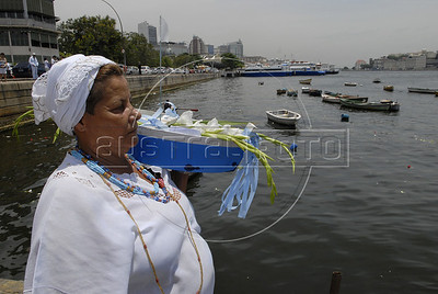 A devote of Afro-Brazilian religions prepares to give offerings into the sea in the Guanabara bay to the African deity of the sea and fertility, Yemanja, Rio de Janeiro, Brazil, February 2, 2011. The festival day corresponds with the Roman Catholic feast of Nuestra Senora de Navegantes, Our Lady of Seafarers, which is also celebrated in Rio de Janeiro. She is also known as the sea-goddess and his devotes give in the sea offerings with flowers, perfumes and wines. Transported by West African slaves to the Americas throughout the hundreds of years of the existence of slavery in the New World. (Austral Foto/Renzo Gostoli)