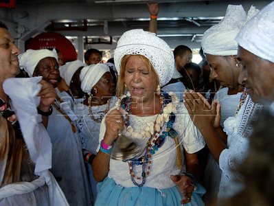 Devotees of Afro-Brazilian religions honor, dancing and singing around flowers and other offerings in a boat at Guanabara bay, the African diety of the sea, Yemanja, Rio de Janeiro, Brazil, February 2, 2010. The festival day corresponds with the Roman Catholic feast of Nuestra Senora de Navegantes, Our Lady of Seafarers, which is also celebrated in Rio de Janeiro. She is also known as the sea-goddess and his devotes give in the sea offerings with flowers, perfumes and wines. Transported by West African slaves to the Americas throughout the hundreds of years of the existence of slavery in the New World. (Austral Foto/Renzo Gostoli)