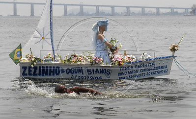 A man swims near a offerings to the African deity of the sea and fertility, Yemanja, in the Guanabara bay, Rio de Janeiro, Brazil, February 2, 2011. The festival day corresponds with the Roman Catholic feast of Nuestra Senora de Navegantes, Our Lady of Seafarers, which is also celebrated in Rio de Janeiro. She is also known as the sea-goddess and his devotes give in the sea offerings with flowers, perfumes and wines. Transported by West African slaves to the Americas throughout the hundreds of years of the existence of slavery in the New World. (Austral Foto/Renzo Gostoli)