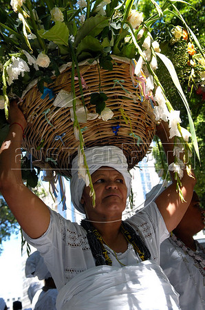 Women devotes of Afro-Brazilian religions give offerings through the streets to the African deity of the sea and fertility, Yemanja, Rio de Janeiro, Brazil, February 2, 2010. The festival day corresponds with the Roman Catholic feast of Nuestra Senora de Navegantes, Our Lady of Seafarers, which is also celebrated in Rio de Janeiro. She is also known as the sea-goddess and his devotes give in the sea offerings with flowers, perfumes and wines. Transported by West African slaves to the Americas throughout the hundreds of years of the existence of slavery in the New World. (Austral Foto/Renzo Gostoli)
