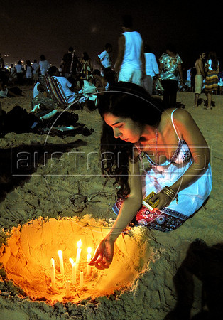A devote of Afro-Brazilian religions lights candels to honor the African deity of the sea and fertility Yemanya, to ask for a lucky 2010, at Copacabana beach, Rio de Janeiro,  Brazil, December 31, 2009.  (Austral Foto/Renzo Gostoli)