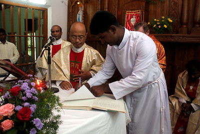 Br. Sajeevan, and witnesses, sign the profession document.