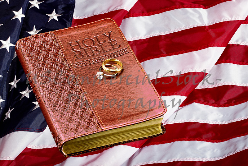 Holy Bible with Wedding Rings on American Flag Concept