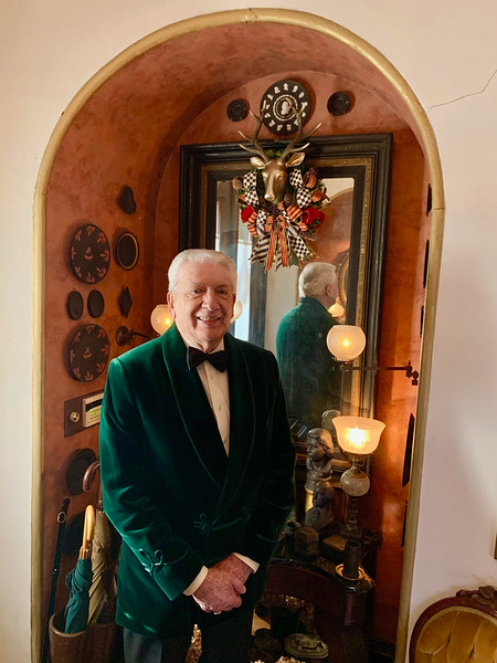 R. Edward Roach is dashing in his  green velvet dinner jacket. The wreath behind is from the famous Harrods of London.