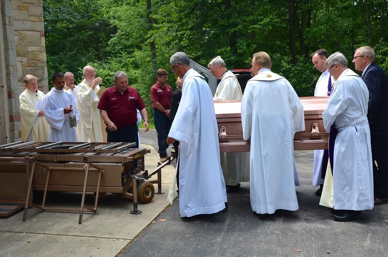 The pallbearers carry Fr. Yost