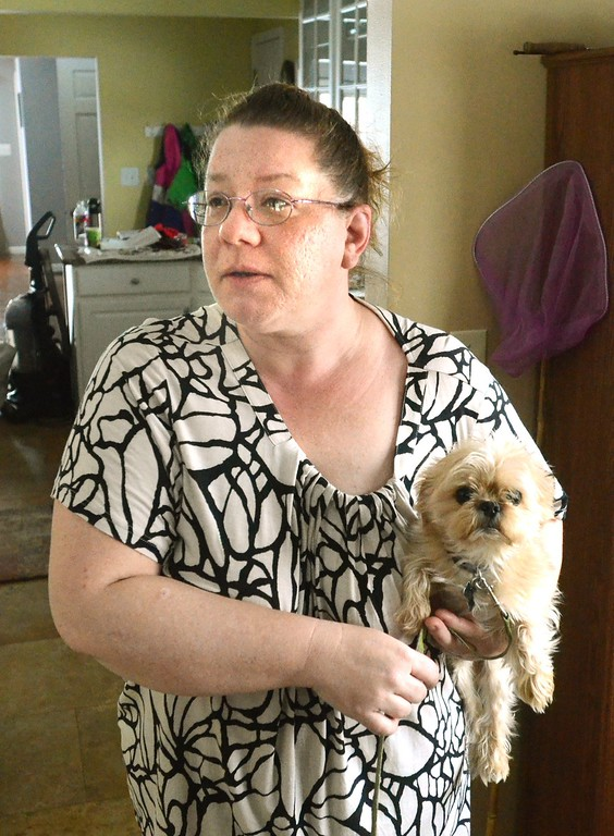 . Jill Hurley, with her dog Fitch, in her Waterford Township home. Fitch lives near the Community Programs Inc, where it is believed that Ruth Pozdol was staying. Pozdol is in police custody for carjacking and the killing of Clifford Van Hayward Sunday.     Monday,  January 19th, 2015.    Tim Thompson-The Oakland Press