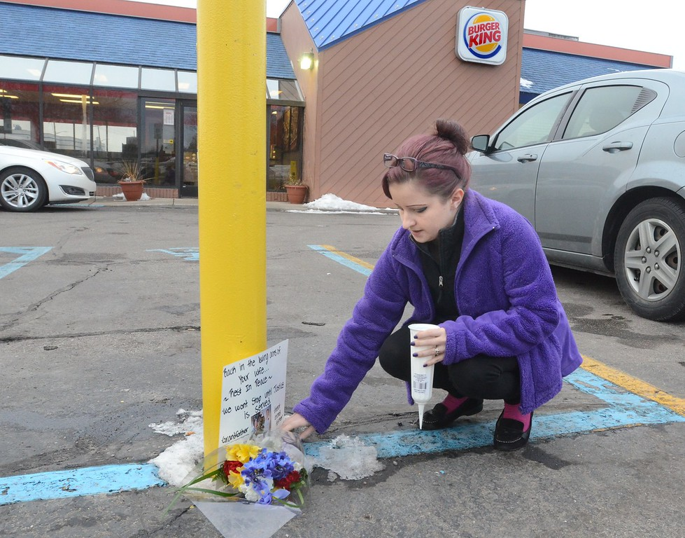 . Amy Davis makes a memorial for her grandfather Clifford Van Haywald at the Burger King Restaurant  in Waterford. Haywald was kill when it is believed that Ruth Pozdol  carjacked and the killed him Sunday.     Monday,  January 19th, 2015.    Tim Thompson-The Oakland Press